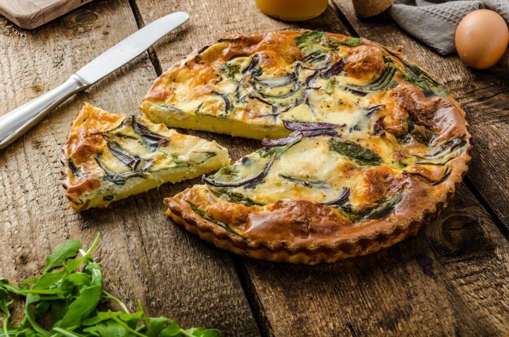 Gemüse-Quiche mit Zwiebeln, Spinat und Rucola